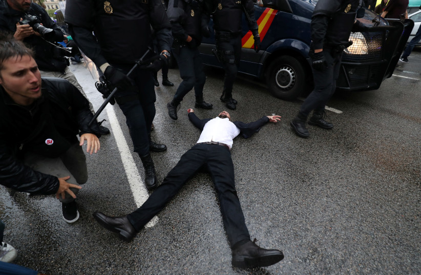 Riot police remove demonstrators outside a polling station for the banned independence referendum in Barcelona, Spain, October 1, 2017. (photo credit: REUTERS)
