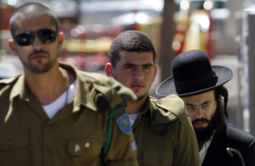 An ultra-Orthodox Jewish man walks behind Israeli soldiers at the entrance to a recruiting office in Jerusalem July 4, 2012.  (photo credit: REUTERS)