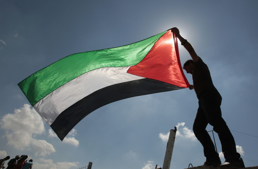 A Palestinian holds a flag during a protest (photo credit: REUTERS)