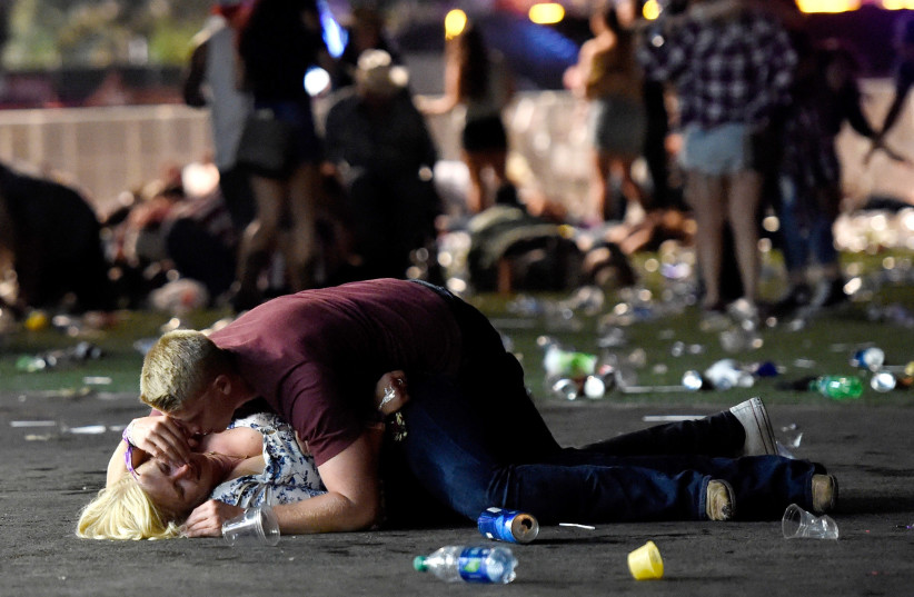 LAS VEGAS, NV - OCTOBER 01: A man lays on top of a woman as others flee the Route 91 Harvest country music festival grounds after a active shooter was reported on October 1, 2017 in Las Vegas, Nevada. (photo credit: DAVID BECKER/GETTY IMAGES/AFP)