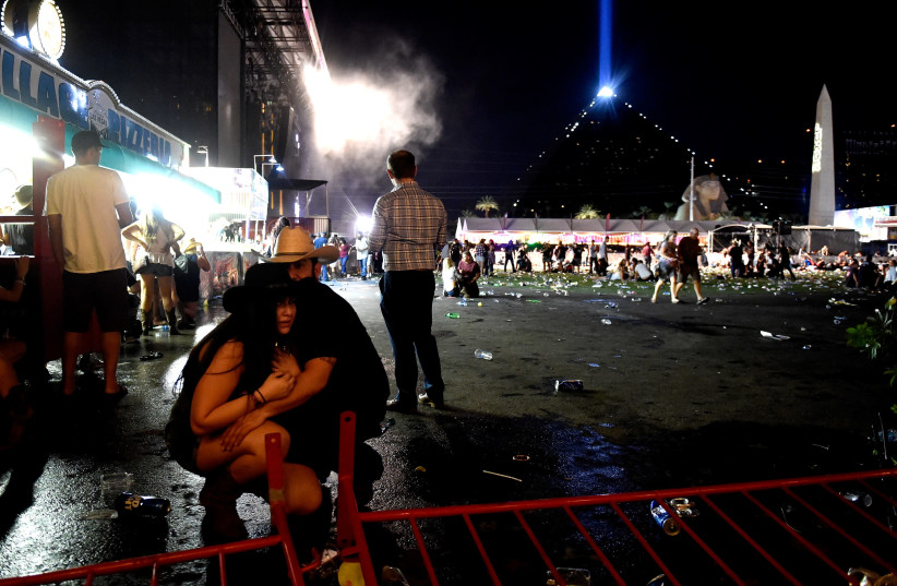 People take cover at the Route 91 Harvest country music festival in Las Vegas after gun fire was heard (photo credit: DAVID BECKER/GETTY IMAGES/AFP)