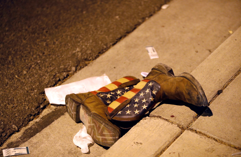 A pair of cowboy boots in the street outside the concert venue after a mass shooting in Las Vegas, Nevada (photo credit: STEVE MARCUS/REUTERS)