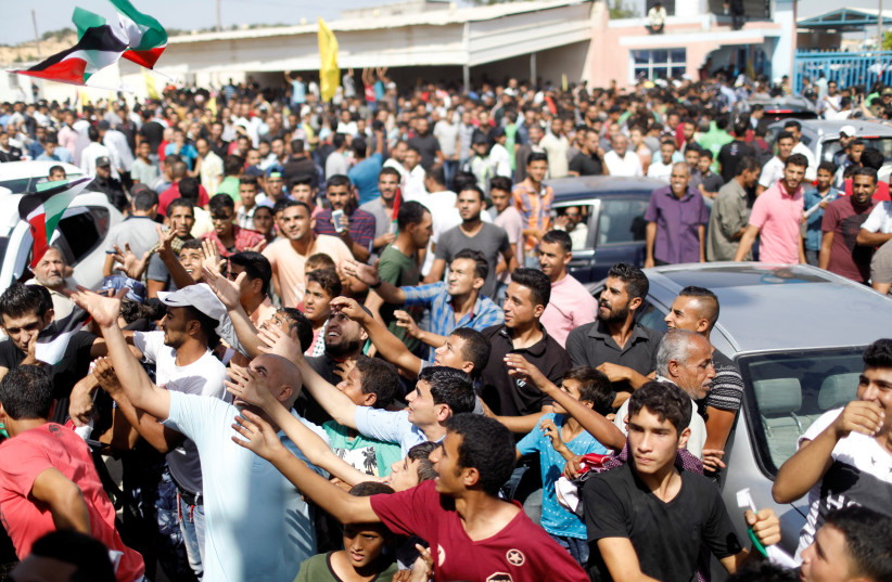 Palestinians celebrate the arrival of Palestinian Authority Prime Minister Rami Hamdallah and his government to take control of Gaza from the Islamist Hamas group (photo credit: SUHAIB SALEM / REUTERS)