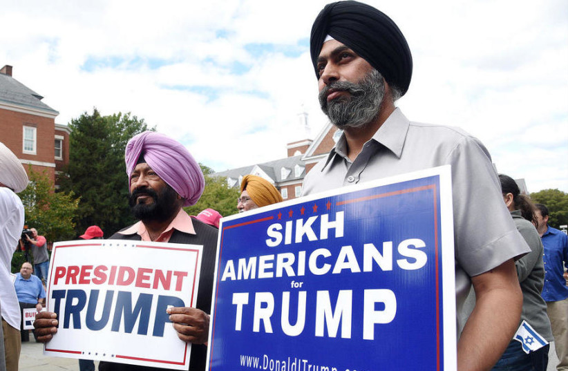 Sikh Trump supporters Manjit Singh Kario, left, and Dilvis Singh hold signs during a Making America Great Again, Already! Unity In Diversity for President Donald Trump rally at Lawyers' Mall in Annapolis, Maryland. (photo credit: PAUL W. GILLESPIE/CAPITAL GAZETTE)