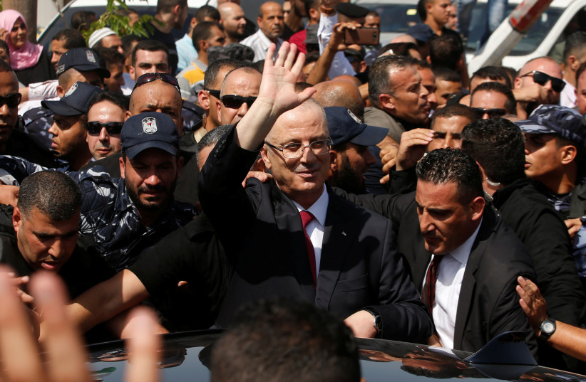 Palestinian Prime Minister Rami Hamdallah waves upon his arrival with his government ministers to take control of Gaza from the Islamist Hamas group (photo credit: MOHAMMED SALEM/ REUTERS)