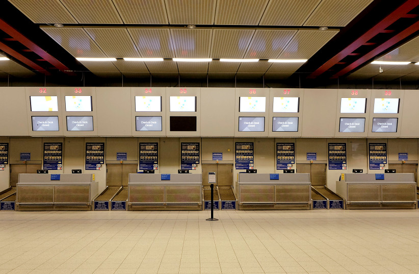 Check-in desks stand empty in the Monarch flights departures area after the airline ceased trading, at Luton airport, Britain October 2, 2017. (photo credit: MARY TURNER / REUTERS)