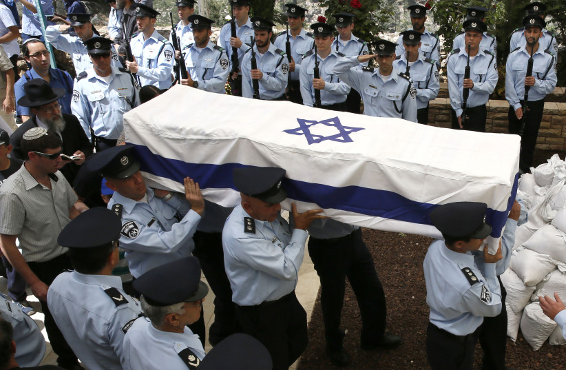 Israeli police officers carry the coffin, draped in the Israeli flag, of slain Chief Superintendent Baruch Mizrahi (photo credit: GALI TIBBON / AFP)