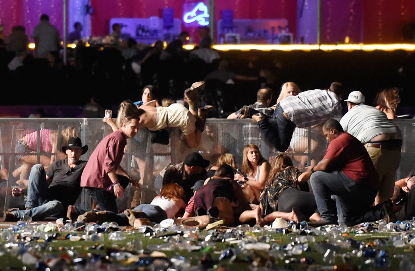 People scramble for shelter during a mass shooting at a music festival in Las Vegas (photo credit: DAVID BECKER/GETTY IMAGES/AFP)