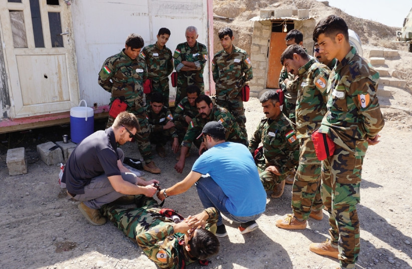 AN FAI VOLUNTEER shows Peshmerga how to apply a tourniquet at a base at Hawija, Iraq. (photo credit: SETH J. FRANTZMAN)
