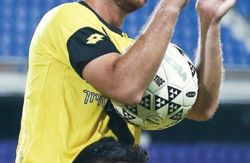 Maccabi Netanya forward Diya Saba received the match ball after scoring a hat-trick in last night's 4-0 win over Maccabi Petah Tikva in Premier League action (photo credit: REUTERS)