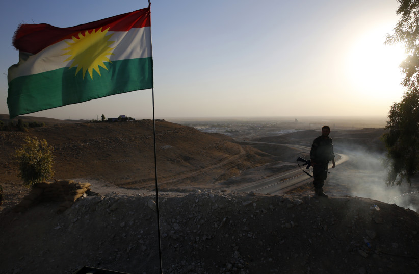 A Kurdish Peshmerga fighter looks down the road to Makhmur  (photo credit: AHMED JADALLAH / REUTERS)