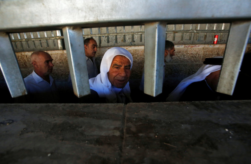 Palestinians cross an Israeli checkpoint in the West Bank city of Bethlehem (photo credit: MUSSA QAWASMA / REUTERS)