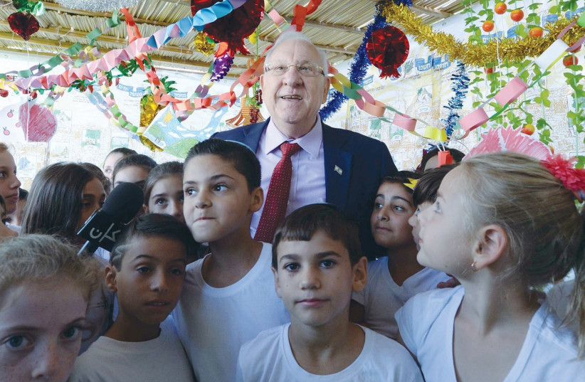 PRESIDENT REUVEN RIVLIN is joined by fourth-grade pupils from the Ariel mixed religious-secular school in the capital's Gilo neighborhood, who are there to help him decorate the sukka at the President's Residence. (photo credit: MARK NEYMAN/GPO)