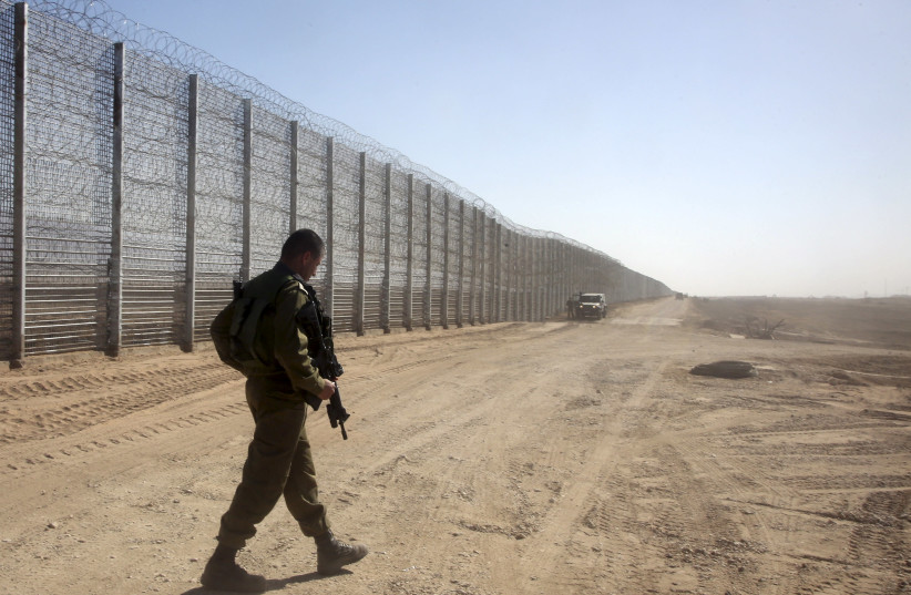 An Israeli soldier walks next to the border fence between Israel and Jordan, in southern Israel near Eilat February 9, 2016. (photo credit: REUTERS/MARC ISRAEL SELLEM)