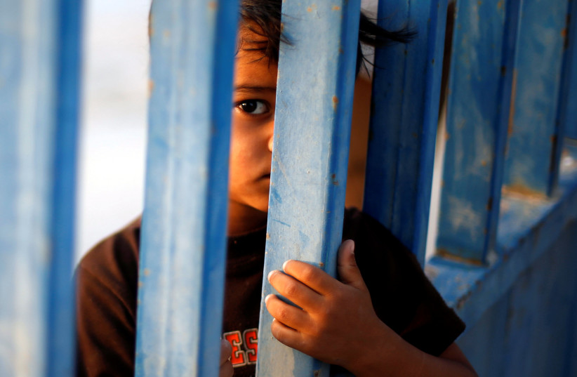 A Palestinian boy standing by a gate looks on as he waits for the return of his relatives after performing the annual Haj pilgrimage in Mecca, at Rafah border crossing in the southern Gaza Strip, September 13, 2017 (photo credit: REUTERS/MOHAMMED SALEM)