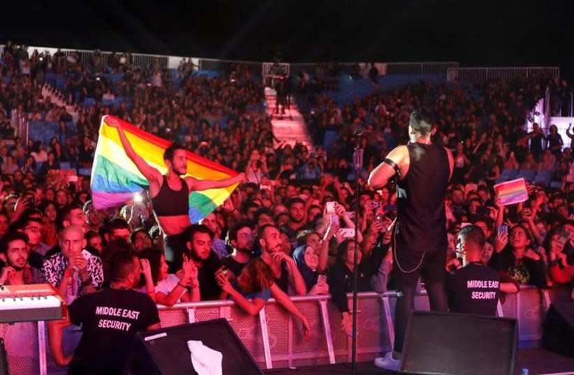 A fan of Lebanese alternative rock band Mashrou' Leila holds a rainbow flag during their concert at the Ehdeniyat International Festival in Ehden town, Lebanon August 12, 2017.  (photo credit: REUTERS/JAMAL SAIDI)