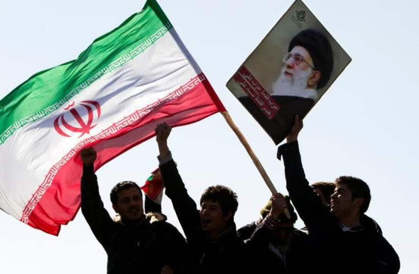Demonstrators wave Iran's flag and hold up a picture of supreme leader Ayatollah Ali Khamenei during a ceremony to mark the 33rd anniversary of the Islamic Revolution, in Tehran's Azadi square February 11, 2012. (photo credit: REUTERS/RAHEB HOMAVANDI)