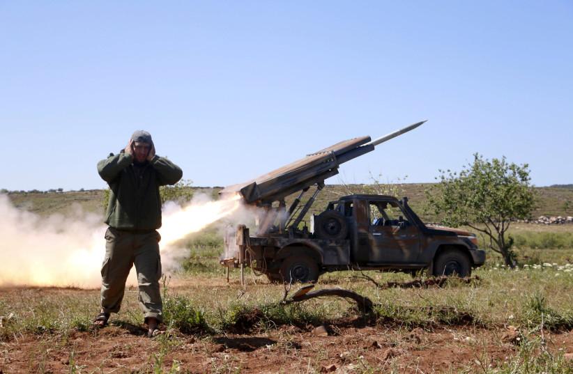 A Syrian rebel fires at forces loyal to Bashar Assad in Idlib, Syria  (photo credit: STRINGER/ REUTERS)