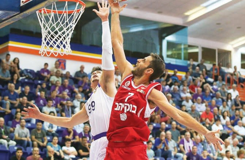 Hapoel Jerusalem's Greek forward Stratos Perperoglou (right) scores two of his six points during his BSL debut last night, beating Ironi Nahariya's Yiftach Ziv to the basket in the 76-68 win at Ein Sara. (photo credit: ERAN LUF)