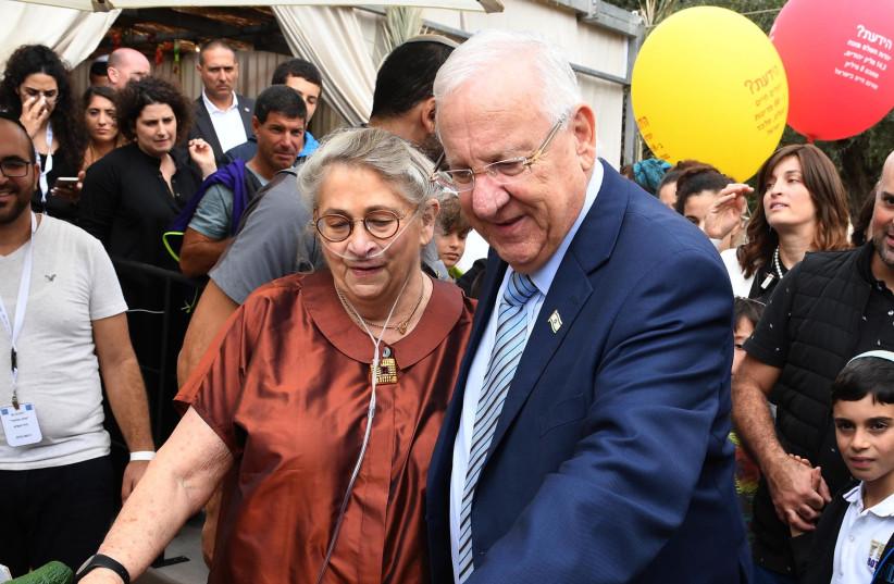 President Rivlin and his wife Nechama greet Israelis in his Jerusalem Sukka. (photo credit: Mark Neiman/GPO)