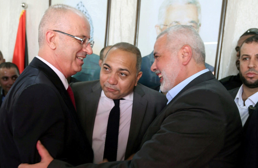 PALESTINIAN AUTHORITY Prime Minister Rami Hamdallah (left) shakes hands with Hamas chief Ismail Haniyeh in Gaza City on October 2. (photo credit: IBRAHEEM ABU MUSTAFA / REUTERS)