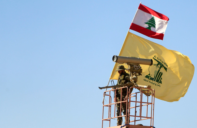 A Hezbollah fighter stands at a watch tower at Juroud Arsal, the Syria-Lebanon border (photo credit: REUTERS)
