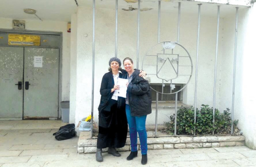 A FORMER 'chained' woman (left) stands in front of a rabbinic court with her lawyer after winning her case. (photo credit: Courtesy)