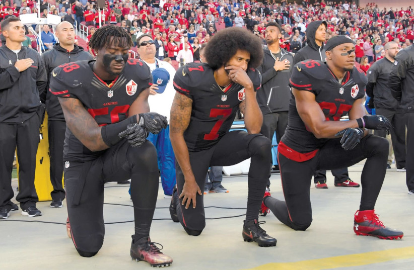 SAN FRANCISCO 49ERS outside linebacker Eli Harold (58), quarterback Colin Kaepernick (7) and free safety Eric Reid (35) kneel in protest during the playing of the national anthem before a NFL game in Santa Clara, California. (photo credit: KIRBY LEE/USA TODAY/VIA REUTERS)