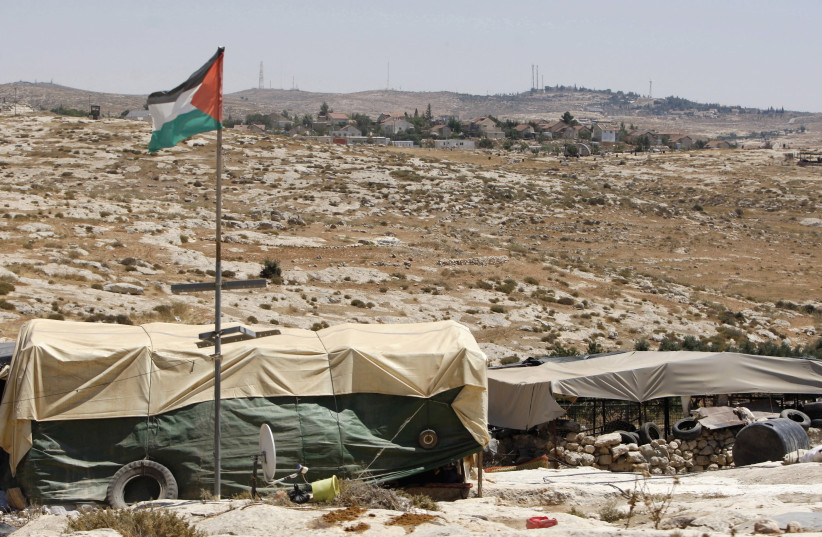 TENTS AND a Palestinian flag at the Beduin community of Susiya (photo credit: REUTERS)