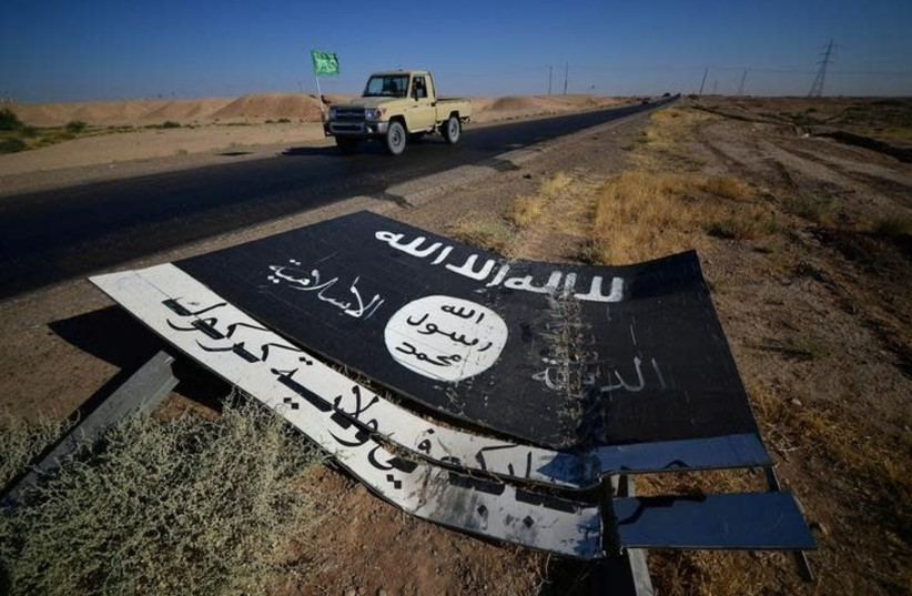 A black sign belonging to Islamic State militants is seen on the road in Al-Al-Fateha military airport south of Hawija, Iraq, October 2, 2017. (photo credit: REUTERS/STRINGER)