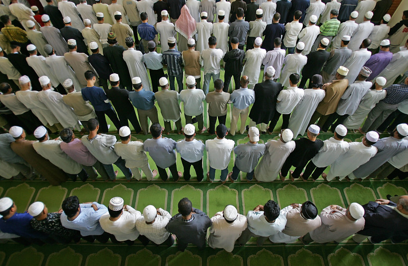 British muslims pray during Friday prayer at the East London mosque. (photo credit: ODD ANDERSEN / AFP)