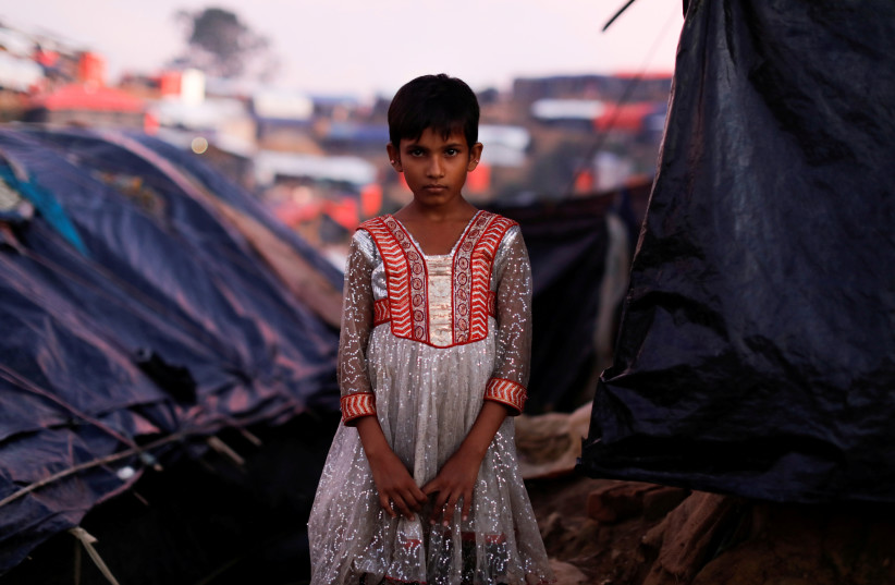 Mujan Begum, a 8-year-old Rohingya refugee, who arrived one month ago with her family poses outside her makeshift tent at a refugee camp near Cox's Bazar, Bangladesh October 11, 2017. (photo credit: REUTERS)
