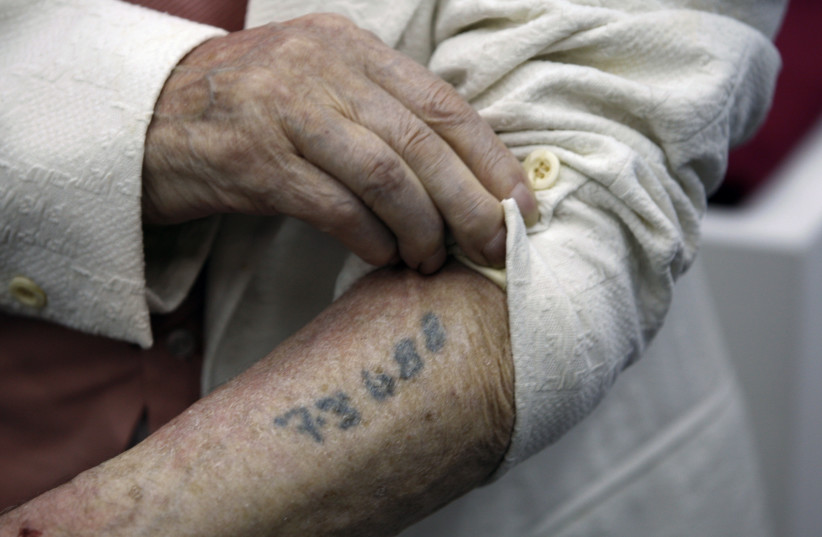 Polish-born Holocaust survivor Meyer Hack shows his prisoner number tattooed on his arm during a news conference at the Yad Vashem Holocaust Museum in Jerusalem June 15, 2009. (photo credit: REUTERS)