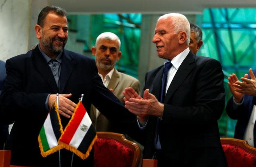 Head of Hamas delegation Saleh Arouri and Fatah leader Azzam Ahmad sign a reconciliation deal in Cairo, Egypt, October 12, 2017. (photo credit: REUTERS/AMR ABDALLAH DALSH)