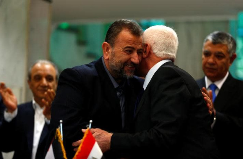 Head of Hamas delegation Saleh Arouri hugs Fatah leader Azzam Ahmad as they sign a reconciliation deal in Cairo, Egypt, October 12, 2017. (photo credit: REUTERS/AMR ABDALLAH DALSH)
