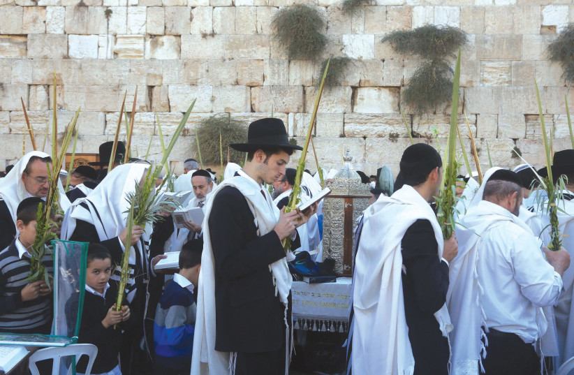 Men praying at the Western Wall on Sukkot. (photo credit: MARC ISRAEL SELLEM/THE JERUSALEM POST)