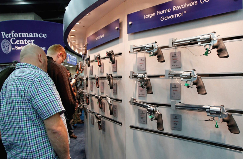 GUN ENTHUSIASTS look over Smith & Wesson guns at the National Rifle Association's annual meetings and exhibits show in Louisville, Kentucky, last year. (photo credit: JOHN SOMMERS II / REUTERS)