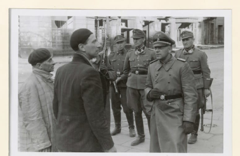 An SS officer questions two Jewish resistance fighters in the Warsaw Ghetto, 1943 (photo credit: Wikimedia Commons)