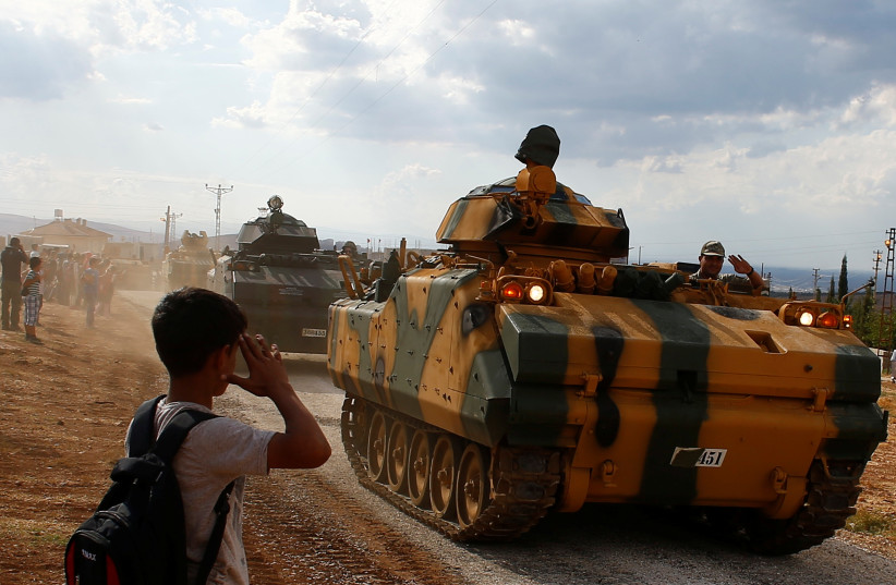 A boy salutes as Turkish Armed Forces vehicles drive pass by a village on the Turkish-Syrian border line in Reyhanli, Hatay province, Turkey October 11, 2017.  (photo credit: REUTERS/OSMAN ORSAL)