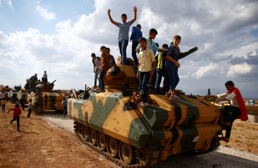 Boys stand on top of a Turkish army vehicle as a military convoy pass by their village on the Turkish-Syrian border line in Reyhanli, Hatay province, Turkey, October 11, 2017.  (photo credit: REUTERS/OSMAN ORSAL)