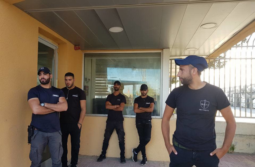 Security guards prevent employees from entering the Negev Ceramics plant. From the Facebook page of Hanna Brig (photo credit: FACEBOOK)