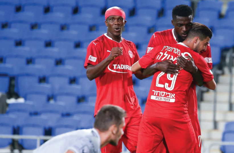Hapoel Beersheba's John Ogu and Amir Khalaila (29), who both scored in last night's 3-1 win over Hapoel Ra'anana, embrace after the former's goal, with Anthony Nawkaeme joining in the celebration (photo credit: DANNY MARON)