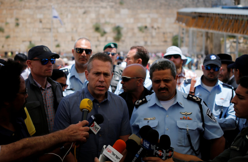 Israel's Public Security Minister Gilad Erdan (3rd L) and police commissioner Roni Alsheich (3rd R) speak to members of the media at the Western Wall in Jerusalem's Old City (photo credit: REUTERS/AMIR COHEN)
