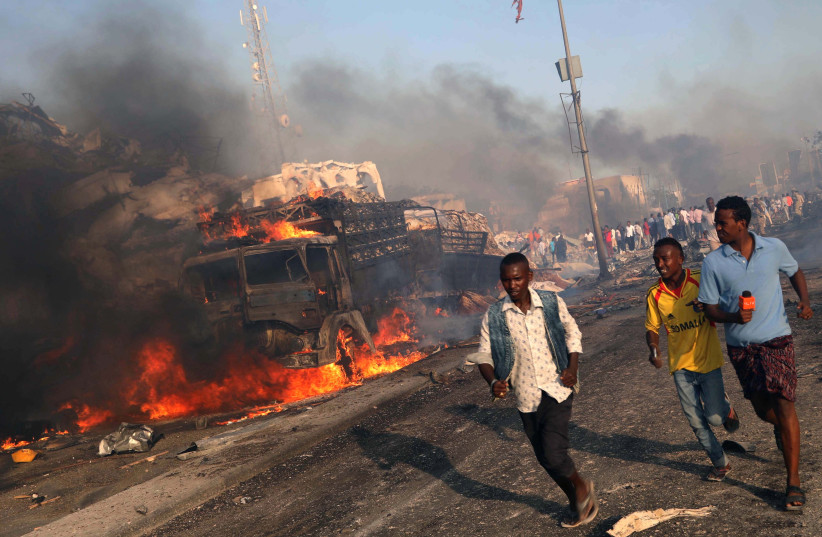 Civilians evacuate from the scene of an explosion in KM4 street in the Hodan district of Mogadishu, Somalia October 14, 2017. (photo credit: FEISAL OMAR/REUTERS)
