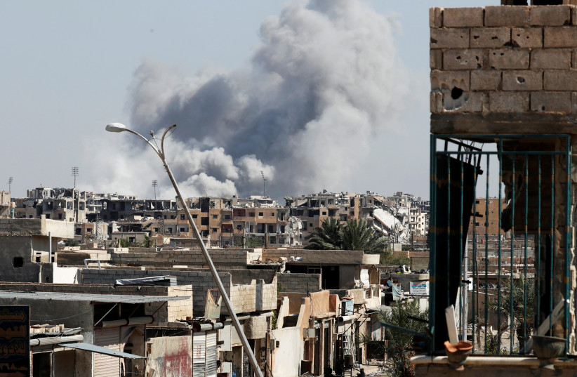 Smoke rises near the stadium where the Islamic State militants are holed up after an air strike by coalition forces at the frontline, in Raqqa, Syria  (photo credit: ERIC DE CASTRO/ REUTERS)