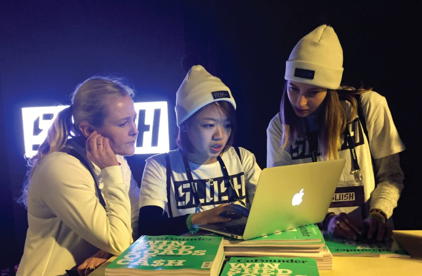 Staff work at Slush, one of Europe's biggest tech start-up conferences, in Helsinki, Finland, last year. According to Israel's Central Bureau of Statistics, women make up more than 35% of the nation's hi-tech workforce. (photo credit: REUTERS)