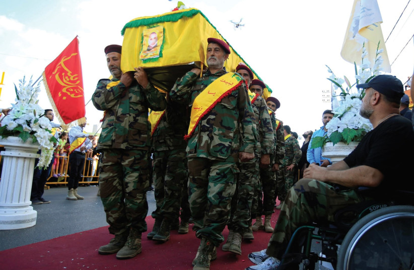 Hezbollah members carry the coffin recently of a senior commander near Nabatieh in southern Lebanon. (photo credit: REUTERS)