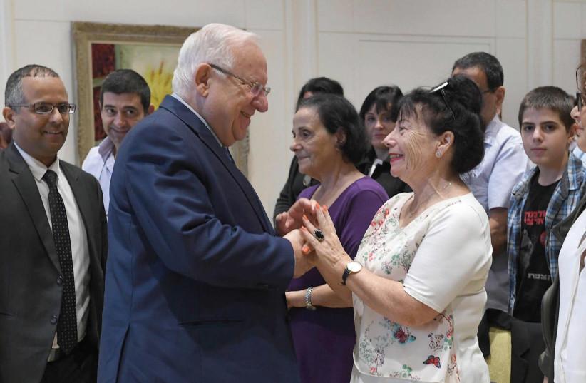 PRESIDENT REUVEN RIVLIN greets Noa Mansura, the mother of Shlomi Mansura from Nahariya, at the President's Residence in Jerusalem yesterday.  (photo credit: Mark Neiman/GPO)