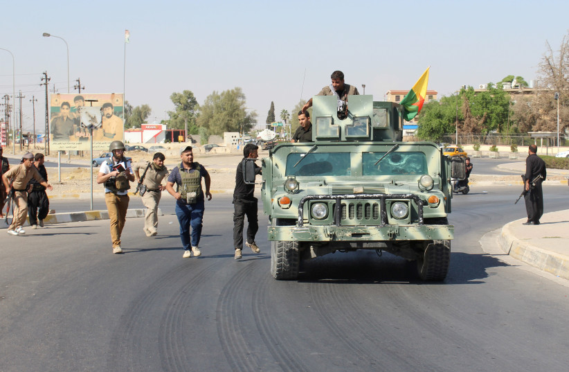 Volunteers and Peshmerga forces carry their weapons north of Kirkuk, Iraq October 16, 2017. (photo credit: REUTERS)