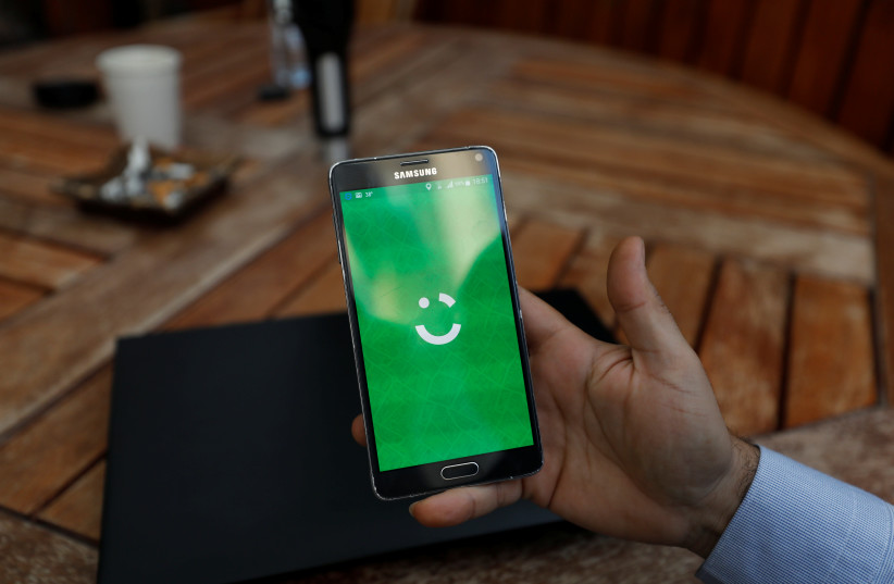 An employee shows the logo of ride-hailing company Careem on his mobile in his office in the West Bank city of Ramallah. (photo credit: REUTERS)